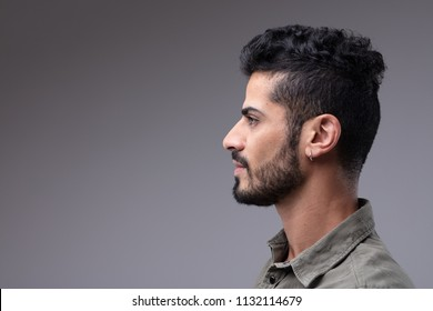 Studio profile portrait of young bearded man with earing