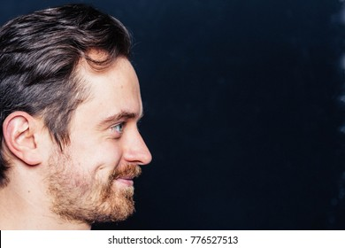 Studio profile portrait of a young pretty man smiling and looking to the side against plain studio background