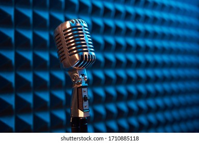 Studio retro condenser microphone on acoustic foam panel background with blue side light, copy space on right