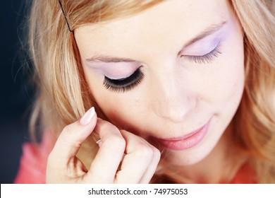 Studio series of doing fashion makeup: applying false eyelashes