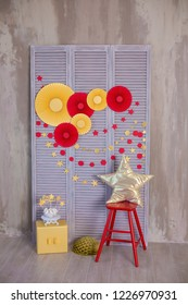 Studio shoot of colorful furniture of chair and wooden stand with amazing red and yellow color paper flowers decorations with golden star handmade pillow