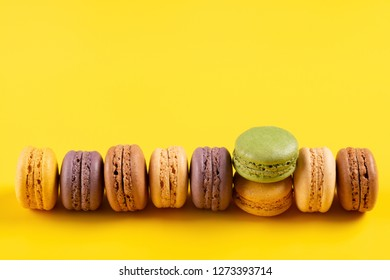 studio shoot of colorful macaroons line up on yellow background