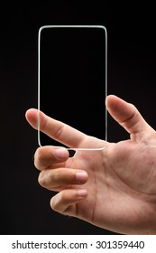 studio shoot of futuristic transparent phone with man hand on black background