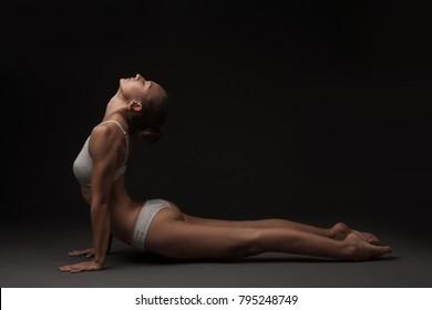studio shoot of healthy latino woman doing yoga isolated over dark studio background