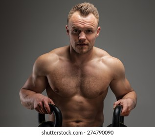 Studio shoot of muscular guy with dumbell on grey background