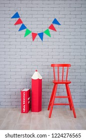 Studio shoot of school book pencil colorful flags on grey brick wall. School study decorations.On red book written on russian - Russian language.