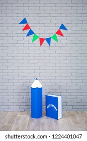 Studio shoot of school book pencil colorful flags on grey brick wall. School study decorations.On blue book written on russian - Literature