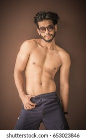 Studio shoot with a shirtless good looking handsome and attractive young male fitness model with abs, strong muscles and long black hair and sunglasses