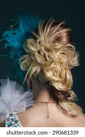 Studio shoot of young woman with creative hairstyle, makeup and dress. Exotic bird