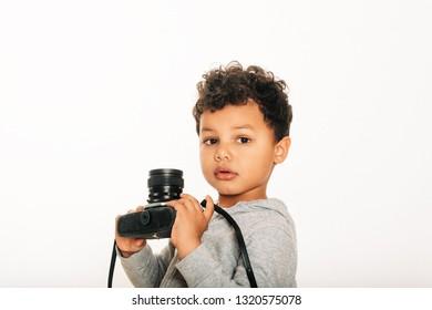 Studio shot of adorable african  toddler boy holding vintage camera