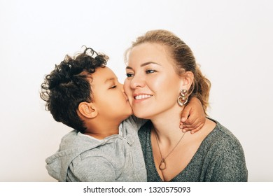 Studio shot of adorable toddler boy giving a kiss to his mother