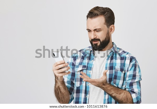 Studio shot of adult bearded brunette male employer, holding gadget in hand and gesturing with perplexed and disappointed expression, standing over gray background. How can somebody make so much
