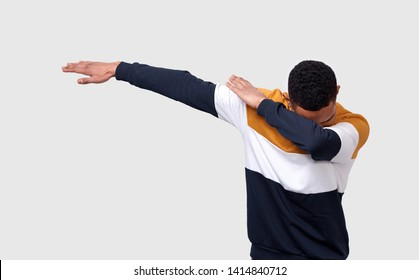 Studio shot of African American young man making dab pulling hands right tilting, covering his head with an arm, dancing and having fun over white background