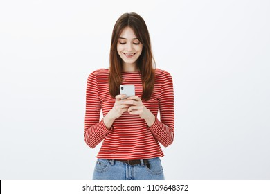 Studio shot of amazed good-looking female freelancer making appointment via smartphone, holding gadget with both hands and smiling joyfully at screen, messaging or watching video in network