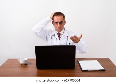 Studio shot of angry Persian man doctor sitting and using laptop computer against white background