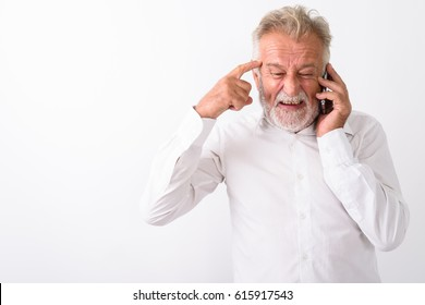 Studio shot of angry senior bearded man thinking while talking on mobile phone against white background
