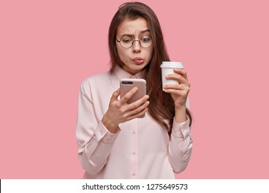 Studio shot of anxious puzzled cute lady reads message from ex boyfriend, reads weird information, holds up to date mobile phone and takeaway coffee, isolated over pink background. Bewilderment