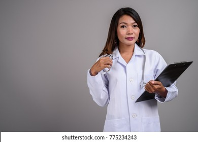 Studio shot of Asian woman doctor against gray background