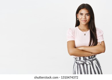 Studio shot of assertive and self-assured good-looking young adolescent girl in skirt and blouse holding hands crossed over chest in confident and ready pose, smiling friendly at camera
