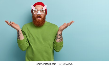Studio shot of astonished puzzled redhead man with thick bristle, wears rabbits glasses with small ears, expresses surprisement, feels uncertain where to celebrate Easter, isolated on blue wall