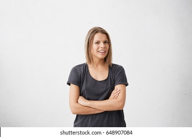 Studio shot of attracive doubtful and dissatisfied young woman having skeptical and suspicious look, keeping arms folded, expressing suspicion or doubt. Human emotions, reaction and attitude