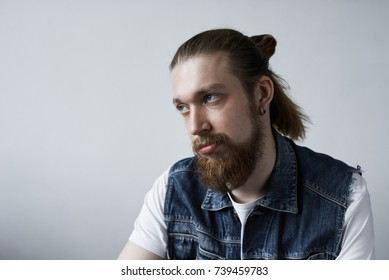 Studio shot of attractive fashionable European student with bushy beard and hair bun rolling eyes while feeling bored during dull tiresome lecture at college. Human facial expressions and emotions