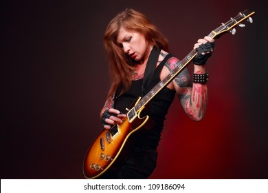 Studio shot of attractive punk girl with lots of tattoos playing electric guitar taken against black paper background with some red highlight