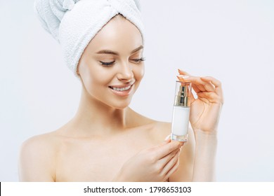 Studio shot of attractive satisfied woman applies moisturizer, holds bottle of skin cream or lotion, wears minimal makeup, poses shirtless against white background, wrapped towel on head. Wellness