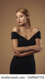 Studio shot of Attractive woman wearing off shoulders black dress - Beauty studio shot of beautiful woman in black dress
