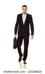 studio shot of attractive young businessman walking with a laptop bag