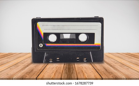 A studio shot of a Audio K7 Cassette tape isolated on a empty room with wooden floor and color background.