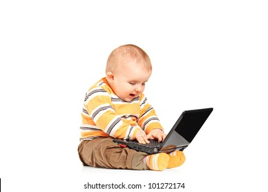 A studio shot of baby boy working on a laptop isolated on white background