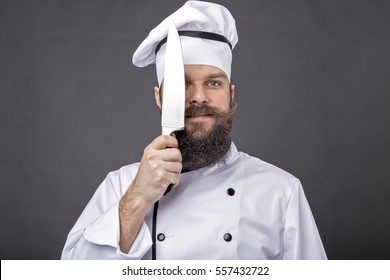 Studio shot of a bearded chef holding a big sharp knife over gray background
