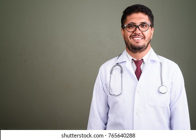 Studio shot of bearded Persian man doctor against colored background