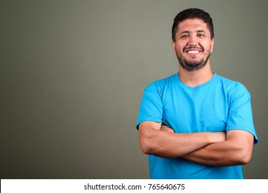 Studio shot of bearded Persian man wearing blue shirt against colored background