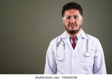 Studio shot of bearded Persian man doctor wearing protective eyeglasses against colored background