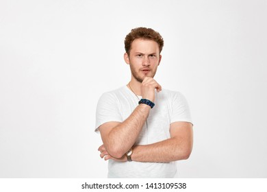 Studio shot of a bearded young man expressing emotion of scepticism while standing over white background. Concept of stress.