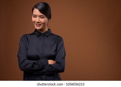 Studio shot of beautiful Asian businesswoman wearing black shirt against brown background
