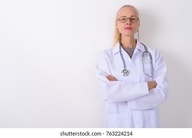 Studio shot of beautiful blond woman doctor with arms crossed against white background