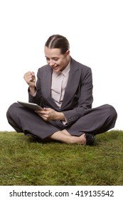Studio shot of a beautiful business woman, sitting crossed legged on the grass, using a tablet computer.  The woman is looking very happy and pleased.  isolated on a white background
