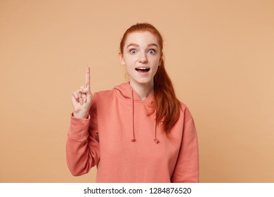 Studio shot of beautiful female raises fore finger as recieves good idea or glad find out something. Ginger girl exited about great thought