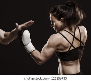 A studio shot of beautiful fitness woman training boxing.