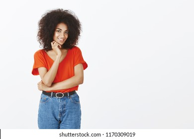 Studio shot of beautiful flirty african american girl with curly hair, smiling with charming expression and holding hand near neck, being intrigued and interested in date with cute guy over grey wall