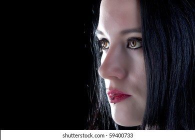 studio shot of a beautiful gothic girl with piercings and brown eyes on black background