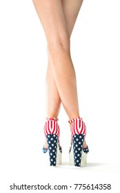 Studio shot of beautiful legs in hot pants in high heels with stars and stripes on white background.