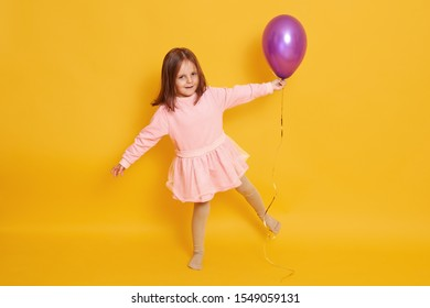 Studio shot of beautiful little girl wih bright purple balloon in hands, child standing on one hand isolated over yellow studio background, female kid wearing rosy dress, celebrating her birthday.