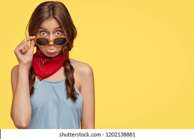 Studio shot of beautiful stylish teenager has two plaits, purses lower lip in discontent, keeps hand on trendy sunglasses, stares with bugged eyes isolated over yellow background with blank copy space