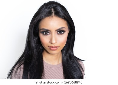 Studio shot of beautiful woman with long black hair isolated against white background