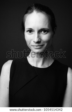58fc161cbea Studio shot of beautiful woman wearing black sleeveless dress against black  background in black and white
