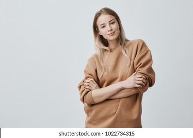 Studio shot of beautiful young woman with blonde straight hair smiling gently while listening to interesting conversation, wearing loose long-sleeved sweater, keeping arms folded. Beauty and youth
